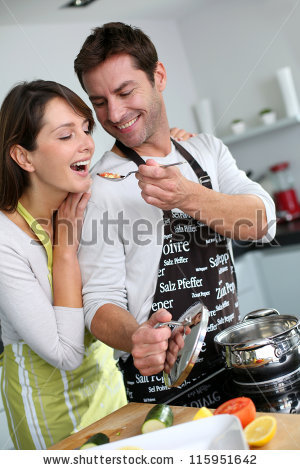 stock-photo-man-preparing-dinner-and-making-her-wife-taste-the-food-115951642